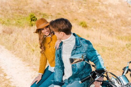 smiling couple sitting on motorbike and looking at each other on meadow