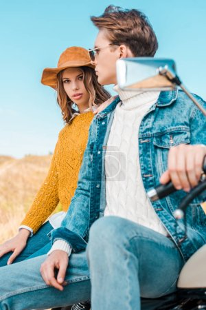 attractive couple sitting on retro motorbike on rural meadow