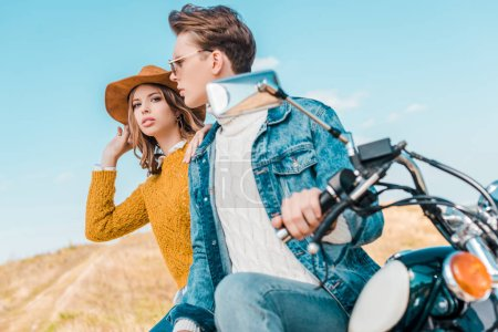 stylish couple sitting on vintage motorbike against blue sky