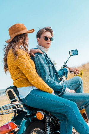 young couple sitting on motorbike and relaxing on rural meadow