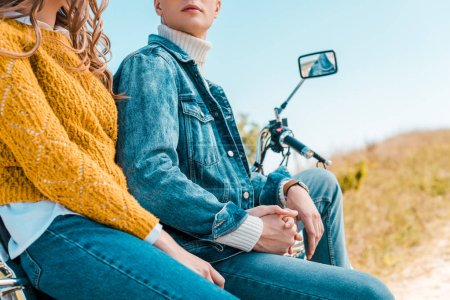 cropped view of couple sitting on vintage motorbike on rural meadow