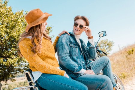 young couple sitting on vintage motorbike and looking at each other