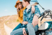 young couple sitting on vintage motorbike on rural meadow