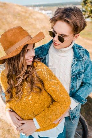 handsome boyfriend hugging beautiful girlfriend on rural meadow