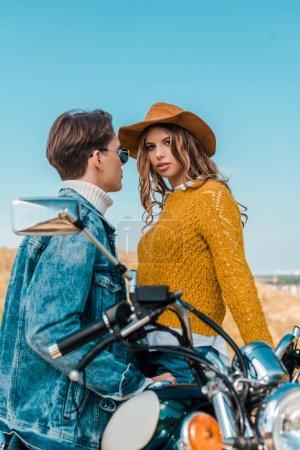 boyfriend sitting on retro motorbike while beautiful girlfriend looking at camera