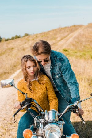 young couple looking on retro motorbike on meadow