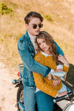 handsome boyfriend hugging beautiful girlfriend and sitting on motorbike