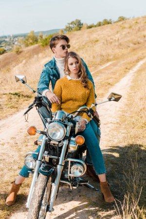 beautiful couple of travelers hugging and sitting on retro motorbike