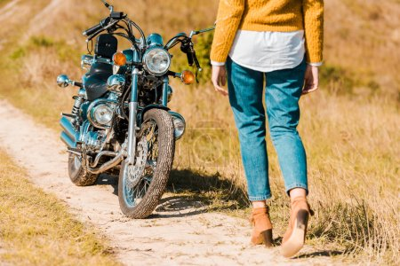cropped view of young woman walking along trail near vintage motorbike