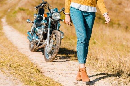 cropped view of young woman walking along trail near retro motorbike