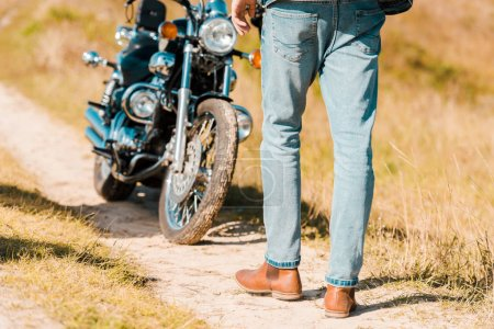 cropped view of man walking along trail near retro motorbike