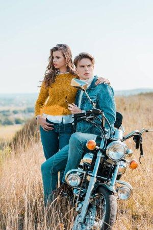 beautiful girlfriend hugging boyfriend and sitting on motorbike