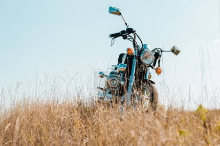 retro motorbike on rural meadow against blue sky