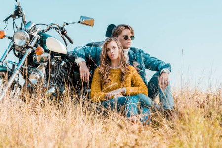 young boyfriend and girlfriend while sitting near motorbike on meadow