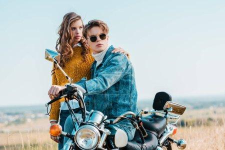 young girlfriend hugging boyfriend while sitting on vintage motorbike