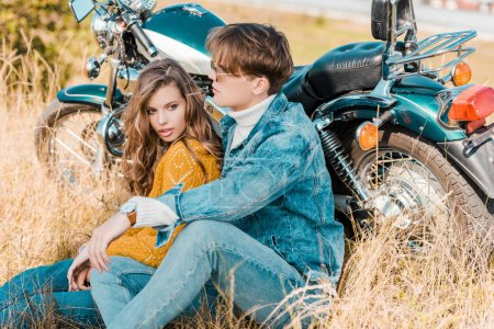 young couple sitting near vintage motorbike on meadow