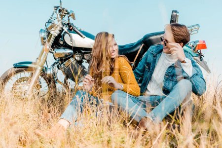 happy couple sitting near vintage motorbike and looking at each other