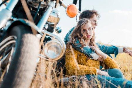 boyfriend hugging girlfriend and sitting near vintage motorbike