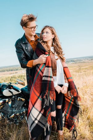 young couple in glasses standing near vintage motorbike and looking at each other