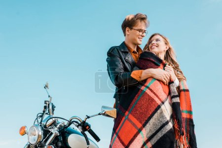 young couple in glasses standing near vintage motorbike against blue sky