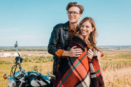 happy couple in glasses standing near vintage motorbike on meadow