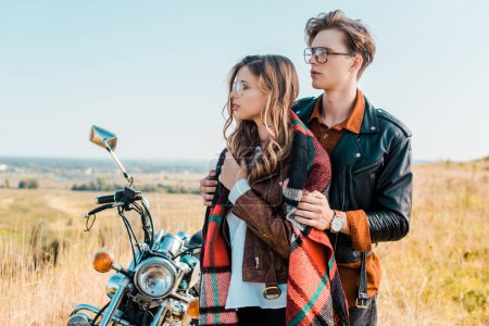 couple in glasses looking away and standing near retro motorbike