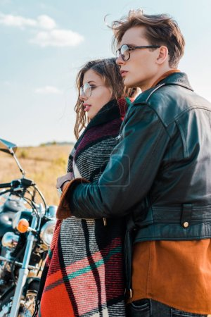 young couple in glasses standing near vintage motorbike and looking away
