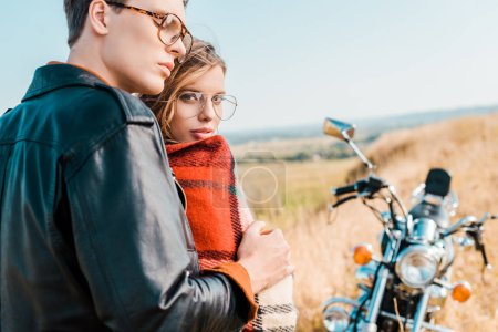 young couple in glasses standing near vintage motorbike