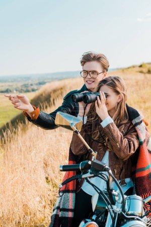 girlfriend looking through binoculars near boyfriend in glasses showing on something