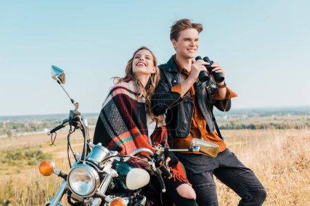 Foto de Novio sonriente sostiene binoculares cerca de novia sentado en moto - Imagen libre de derechos