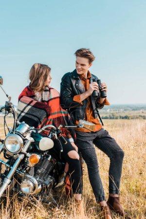 handsome boyfriend holding binoculars and looking at girlfriend sitting on motorbike