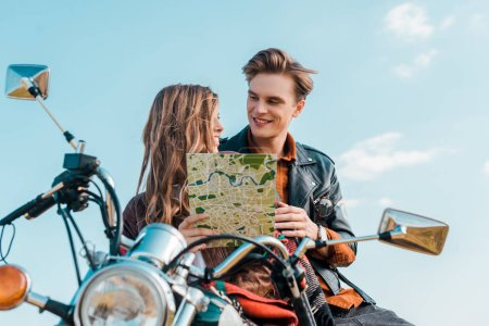 young couple of travelers holding map and sitting on motorbike against blue sky