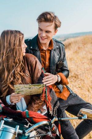 young girlfriend holding map near handsome boyfriend sitting on motorbike