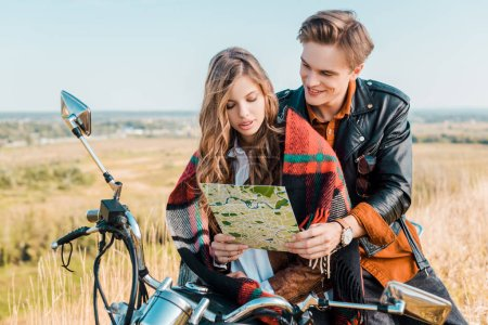 young couple looking on map and sitting on retro motorbike