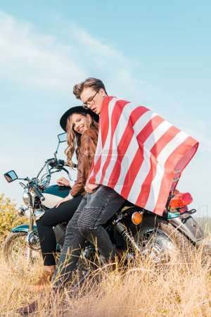 smiling couple with american flag sitting on meadow, independence day concept