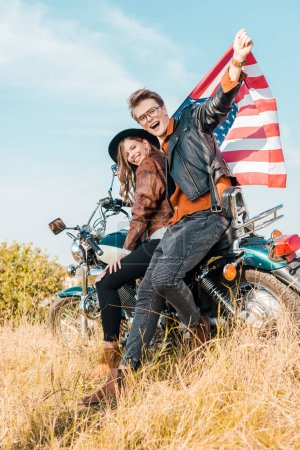 happy couple with american flag sitting on meadow, independence day concept
