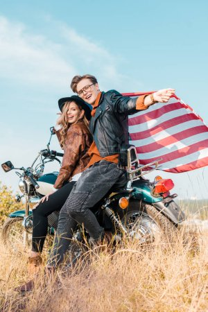 young smiling couple with american flag sitting on motorbike, independence day concept
