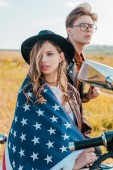 young couple with american flag sitting on motorbike, independence day concept