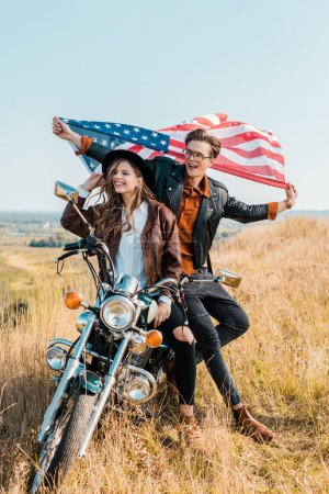 smiling couple with american flag sitting on motorbike, independence day concept