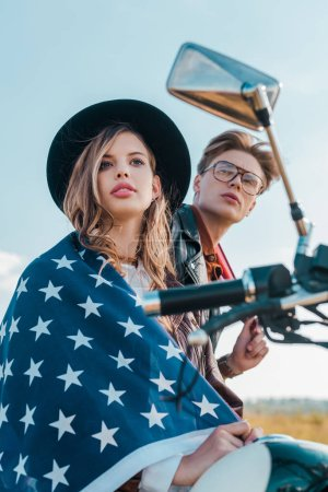low angle view of young couple with american flag, independence day concept