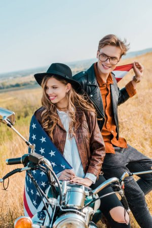 happy couple with american flag sitting on vintage motorbike, independence day concept