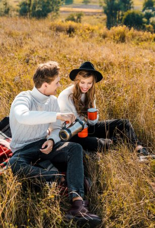 happy couple pouring hot drink from thermos and resting on rural meadow