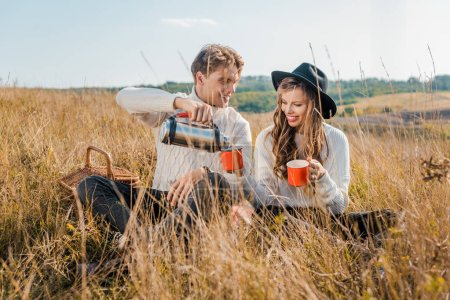 happy boyfriend pouring hot drink from thermos into cups for girlfriend on rural meadow