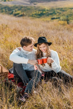 Photo for Young smiling couple clinking with cups and relaxing on rural meadow - Royalty Free Image