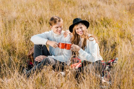 young couple clinking with cups and sitting on plaid on rural meadow