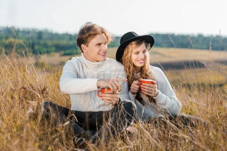 smiling couple with hot drinks looking away on rural meadow