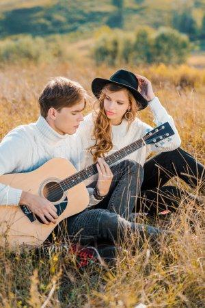 girlfriend looking at boyfriend playing guitar on meadow