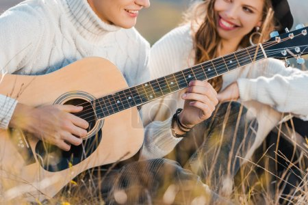 cropped view of smiling couple relaxing on meadow while young man playing guitar