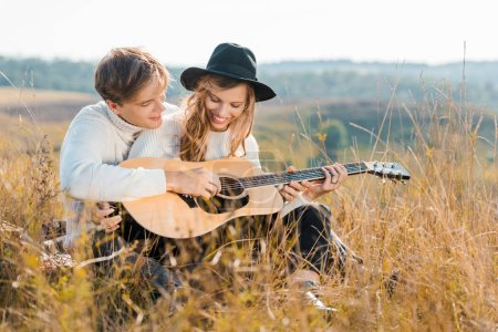 happy couple playing guitar on rural meadow