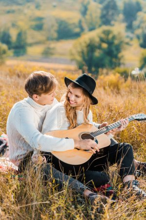 smiling couple playing guitar and resting on meadow